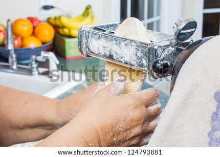 old woman's hands using a pasta machine - stock photo