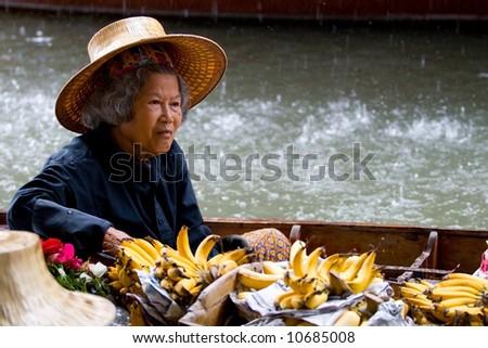 Old woman selling bananas at a traditional Asian floating market near Bangkok, Thailand. - stock photo