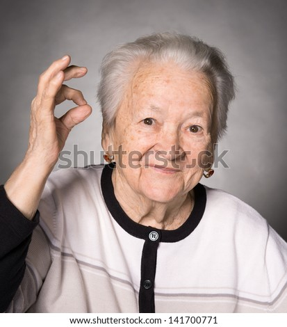 Old woman showing ok sign on a gray background