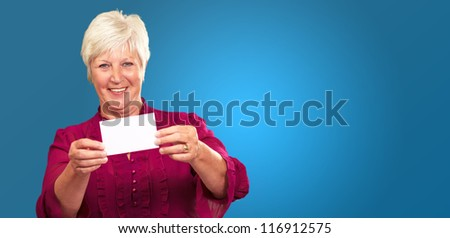 Old Woman Showing  Paper On Blue Background - stock photo