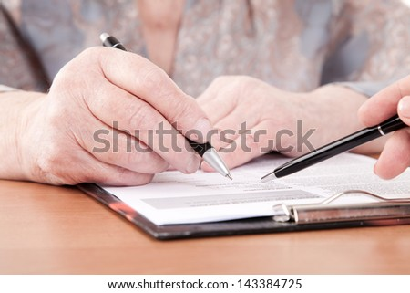 Old woman signs documents