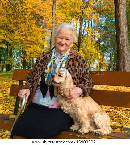 Old woman sitting on a bench with a dog in autumn park - stock photo