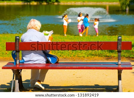 Old woman sitting on bench in park with kids on pond in the background - stock photo