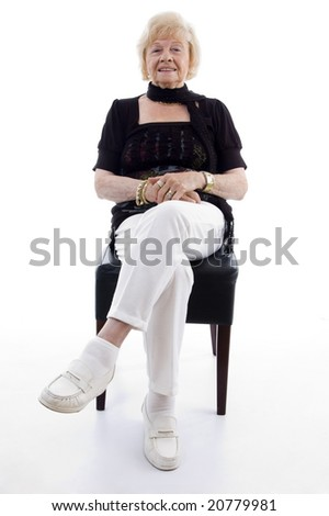 old woman sitting on chair on an isolated background - stock photo