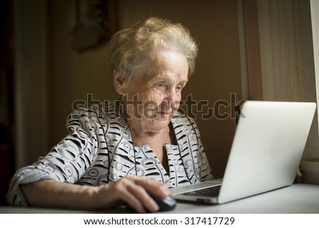 Old woman sitting with laptop at table in his house. - stock photo