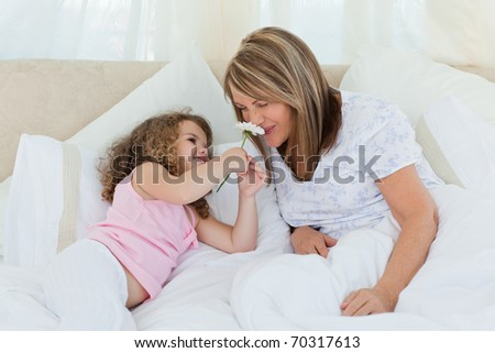 Old woman smelling flower - stock photo