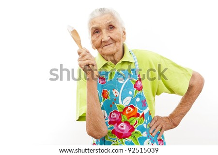 old woman smiling and holding a  rolling pin in her hands