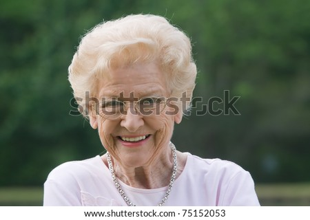 Old woman smiling outside during the day - stock photo
