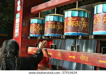 Old woman spining praying luck wheels in Tibetan Buddhist Temple in Sarnath, India - stock photo