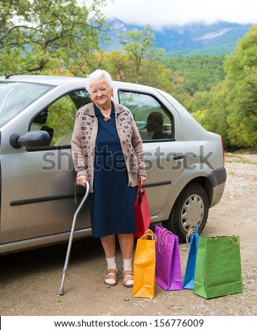 Old woman standing with shopping bags near the car - stock photo