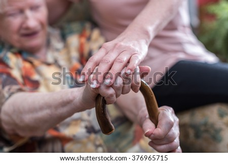 Old woman supported by young woman