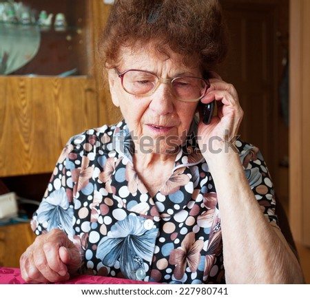 Old woman talking on mobile phone. Elderly, mature female at home - stock photo