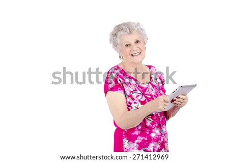 Old woman using a digital tablet against a white background - stock photo