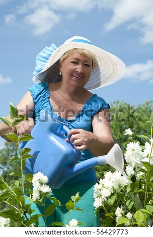 Old woman watering flowers in a garden - stock photo