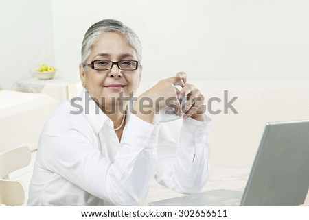 Old woman with a laptop - stock photo