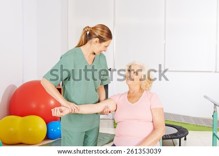Old woman with aching shoulder in physical therapy doing exercises - stock photo