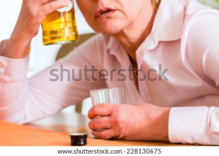 Old woman with alcohol problem sitting at home drinking hard liquor  - stock photo