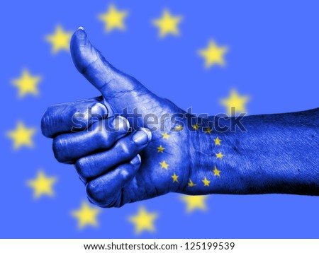 Old woman with arthritis giving the thumbs up sign, wrapped in flag pattern, European Union - stock photo