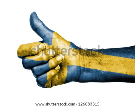 Old woman with arthritis giving the thumbs up sign, wrapped in flag pattern, Sweden - stock photo
