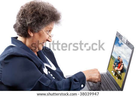 Old woman with glasses using computer - stock photo