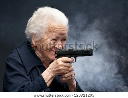 Old woman with pistol on a gray background - stock photo