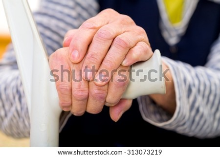 Old womans hands resting on the walking stick - stock photo