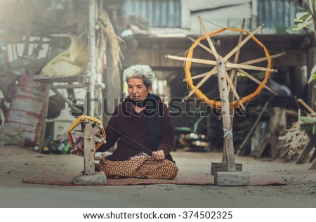 Old women demonstrate to procedure of making Thai Silk weaving - stock photo