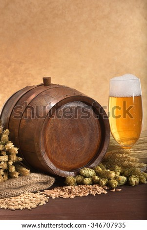 old wood barrel with beer glass, hops, wheat, grain, barley and malt - stock photo