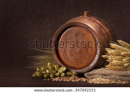 old wood barrel with hops, wheat, grain, barley and malt - stock photo