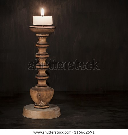 Old wood candlestick with candle.