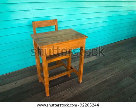 Old wood desk and chair on wood floor and light green wall - stock photo