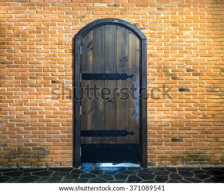 old wood door on red brick wall background - stock photo