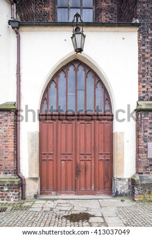 Old wood doors to cathedral. Lantern above. - stock photo
