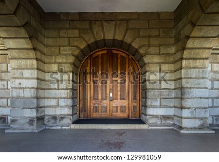 Old wood gate with stone wall - stock photo