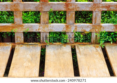 Old Wood long arms chair on plant background and brick floor