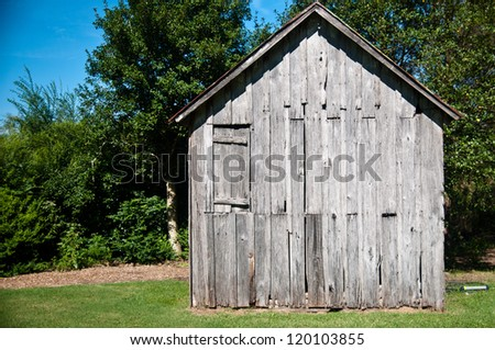 Old wood shack or cabin in the woods against a beautiful bright blue sky - stock photo