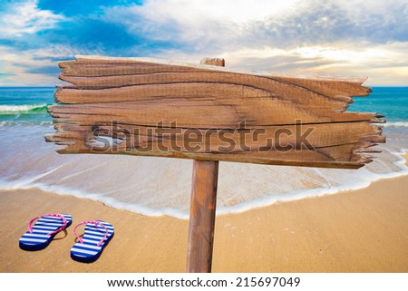 old wood sign on beach - stock photo