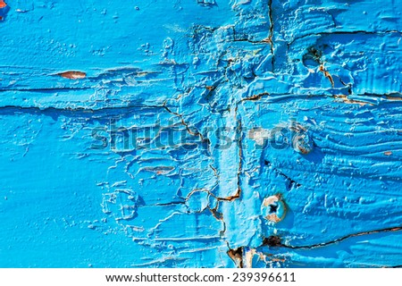 Old wood surface with blue paint flaking and cracking background texture