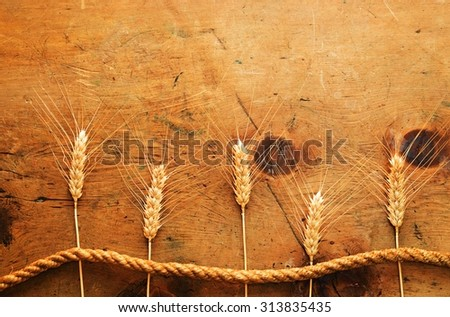 Old wood table with spikelets of wheat and rope makes a frame for a text in rustic vintage style. Top view. Retro concept background. For poster, menu and recipe. - stock photo