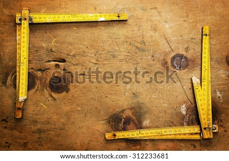 Old wood table with two yardsticks make a frame for text in rustic vintage style. Top view. Retro concept background. - stock photo