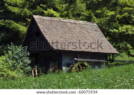 Old wood water mill-house with grass and forest in background. - stock photo