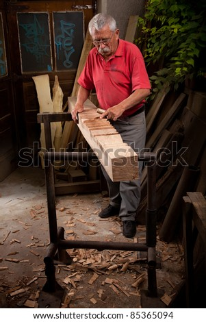Old woodcarver working with mallet and chisel - stock photo