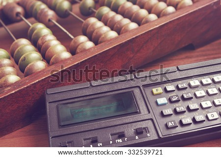 Old wooden abacus and obsolete mathematic  calculator. Retro toned image. - stock photo
