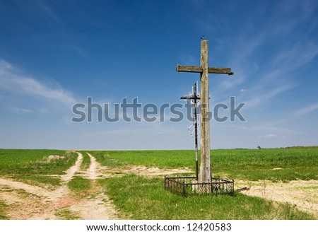 Old wooden and metallic cross at country road. Green grass and blue sky.
