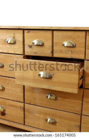 old wooden antique chest of drawers with metal handles, open drawer