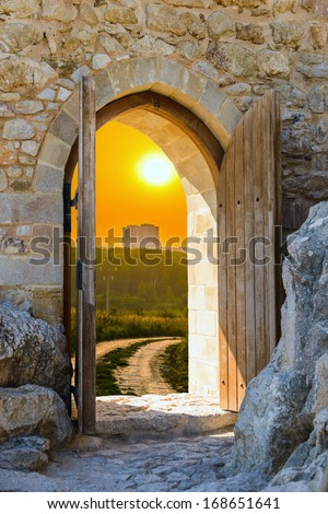 old wooden arch in the fortress with open doors - stock photo