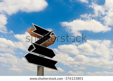 old wooden arrows road sign on sky - stock photo