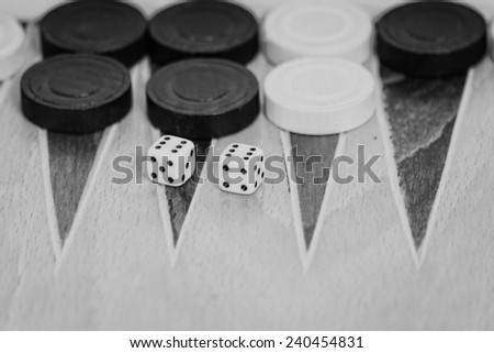 Old wooden backgammon game and dices in black and white - stock photo