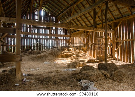 Old wooden barn full of old hay with light shining through the wooden boards. - stock photo