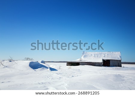 Old wooden barn in Quebec province of Canada. Rural snow scene with snow drifts and blue sky. SPace for your text.  - stock photo